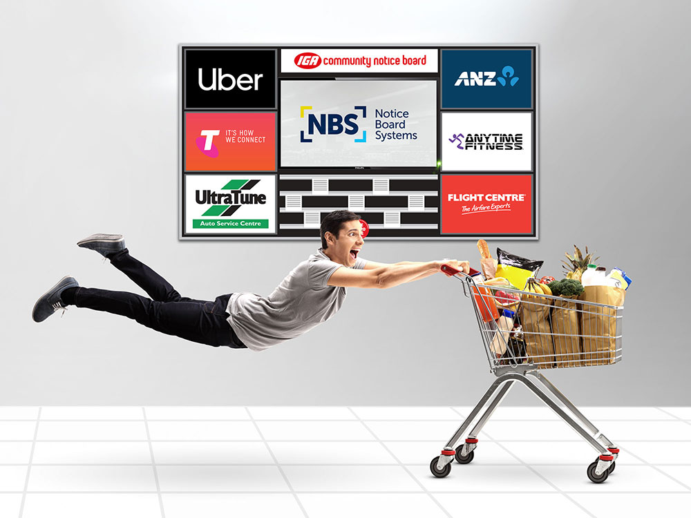 man flying behind shopping trolley in from of Notice Board with multiple advertisements