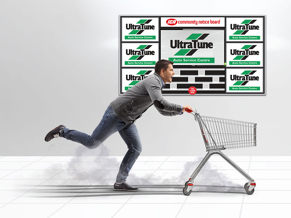 man racing with shopping trolley in from of Notice Board Ultratune advertisement