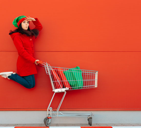 woman in elf outfit in front of a red wall with a shopping trolley